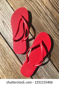 Two red flip flops sitting on weathered wooden boardwalk.