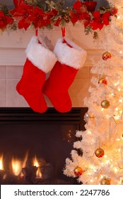 Two red fur stockings hang on the mantle over the fireplace as an antique lighted Christmas tree glows in the evening light.