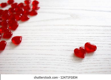 two red glassy hearts on a white wooden background