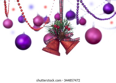 Two red glitter bells hanging on a tartan ribbon with christmas baubles and colored bead chains