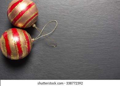 Two red and gold Christmas baubles on a dark slate surface