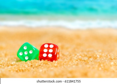 Two red and green dice  in the sand on the background of beach and sea