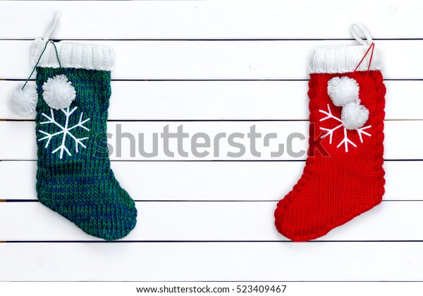 Two red and green snowflake patterned Christmas stockings as borders on white wooden background copy space in middle
