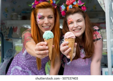 Two red haired ladies smiling wearing vintage spotted dresses holding ice cream out of van with blurred background. Landscape image with text space