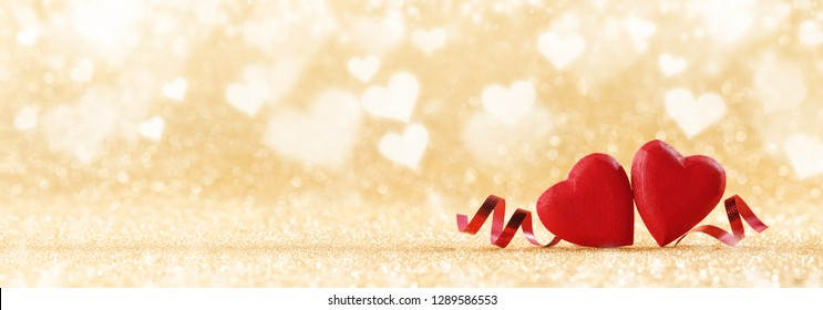 Two red handmade wooden hearts and ribbons on golden bright glitter lights bokeh background