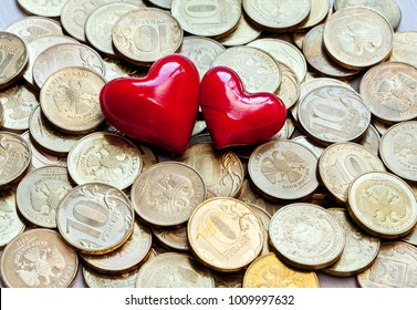 Two red heart on coins showing the advantage of love over money. Love and money symbols