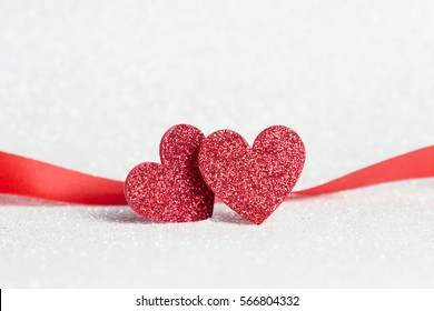 Two red heart shapes on white glitter bokeh light for valentines day background, holidays card with copy space