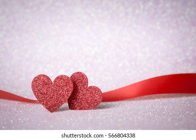 Two red heart shapes on pink glitter bokeh light for valentines day background, holidays card with copy space