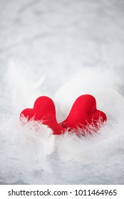 Two red hearts lie on white fluff. Metaphor of love. Greeting card for Valentine's Day. Vertical image