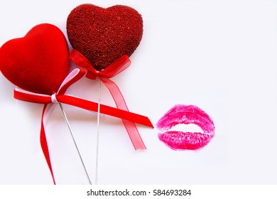 Two red hearts and red lipstick kiss on white background, love letter.