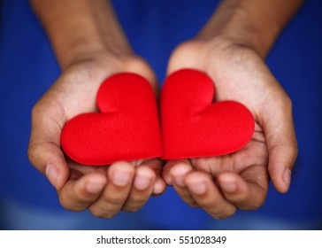 Two red hearts made from velvet fabric lay on young man's hand