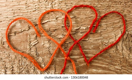 Two red hearts made of red yarn on a textured wooden background. Can be used for the concept of romance, love, engagement, Valentine's Day, marriage, wedding, etc. Close-up.