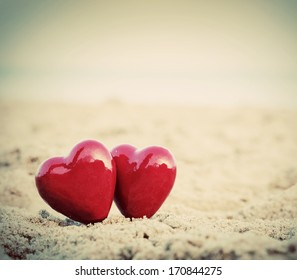 Two red hearts on the beach symbolizing love, Valentine's Day, romantic couple. Calm ocean in the background. Vintage, retro style