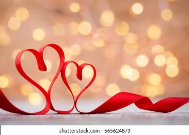 两颗红色的心丝带。 情人节贺卡。