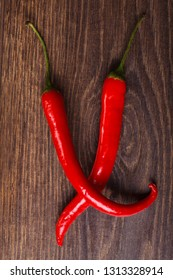 Two red hot chili peppers on a brown wooden table. Mexican, Italian food. Top view. Capsaicin.