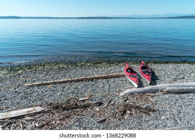 Two red kayaks resting on a driftwood covered rocky pacific northwest beach, mid day.