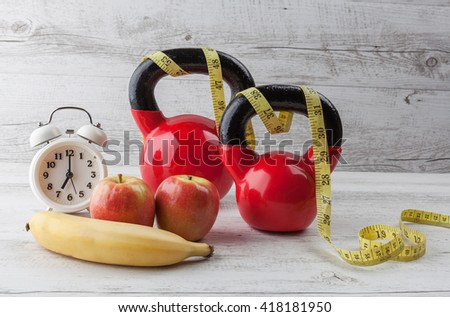Two red kettlebells with measuring tape, apples, banana, and vintage clock on rustic white wooden table. Healthy diet and fitness concept.