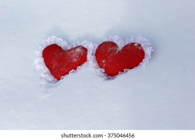 two red lace valentine lie on snow