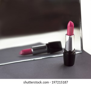 two red lipsticks, perfect versus imperfect symbolic concept idea, detail, macro