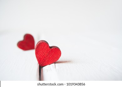 Two red little hearts on white wooden background with copy space. Valentine's day background