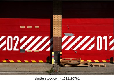 Two red metal roller garage doors numbered one and two