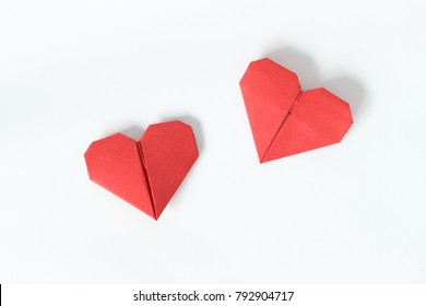 Two red origami hearts on white background. Valentin's Day gift cards. Top view.