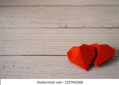 Two red origami paper hearts on wooden white background , Love ,Valentine ,Sweetest day concept with copy space