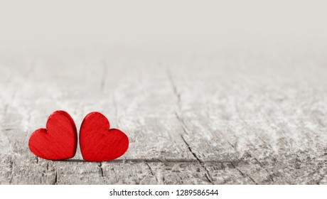 Two red painted handmade hearts on old cracked wooden background with copy space for text