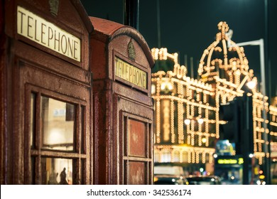 two red phone boxes at night in Knightsbridge against lit shopping centre