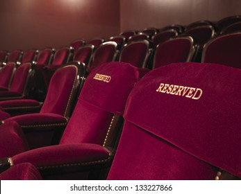 two red reserved theater seats side by side in the middle of others