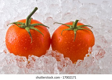 Two red ripe tomatoes resting on a bed of cracked ice.