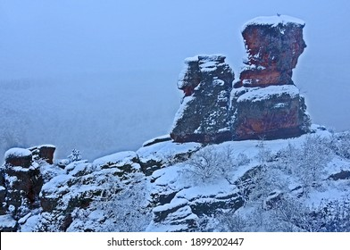 Two red sandstone Belogradchik rocks in Bulgaria under conditions of poor foggy visibility in blizzard