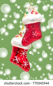 two red santa claus boots over green bokeh background