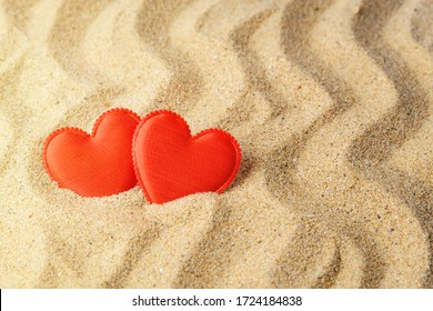 Two red silk hearts on a yellow wavy sea sand. Concept of love, sun, hot summer, sea holiday and vacation on a beach. Top view.