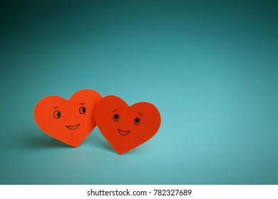 Two red smiling hearts on a blue background. St. Valentine's Day. Couple in love.