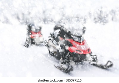 Two red snowmobiles.