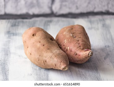 Two red sweet potatoes on a distressed wooden table