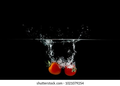 two red tomatoes in water splash on black background