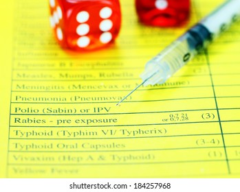 Two red translucent dice placed on a vaccination passport with a loaded syringe next to it, asking the question will you gamble by not having the proper vaccinations!