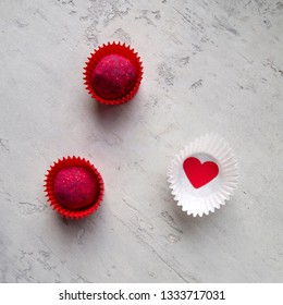 Two red truffles with raspberry filling in red candy wrappers and one white wrapper with a red heart inside on a light grey background. Love concept.