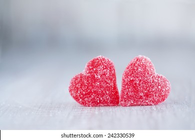Two red Valentines Day candy hearts next to each other