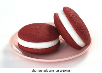 Two Red Velvet Whoopie (or Moon) Pies with Cream Cheese Frosting on White Background