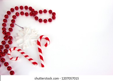 Two red and white candy canes, snowflake and red necklace. Christmas and New Year holiday background concept. Blank space for greetings.
