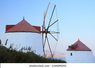 Two red and white traditional windmills in the Chora of Astypalaia