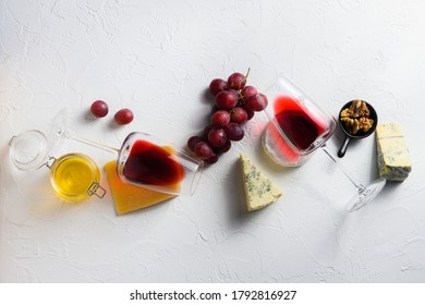 Two red wine glass with assorted cheeses, grapes, nuts over white background, Italian and franch cheese and fruit platter with honey and wine. top view
