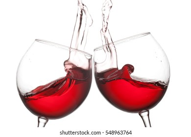 Two red wine glasses and splashing flow on white background. Celebration party concept photo. Macro view photo