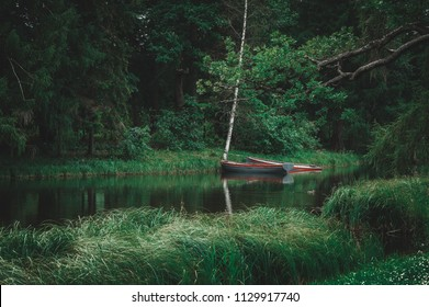 Two red wooden boats moored on lake in grass