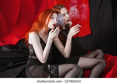Two red-haired girl hugging and smoke on black and red background. Two lesbian women. Long red hair. Beautiful sexy lingerie transparent. Love between girls. Bad habit