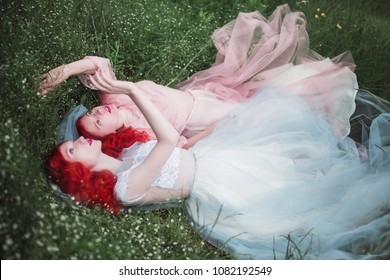 Two red-haired girls in free dresses of tulle on the background of a summer ravine. Two slender models posing in nature
