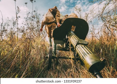 Two Reenactors Dressed As Russian Soviet Red Army Soldiers Of World War II Walking With With Maxim's Machine Gun Weapon In Autumn Meadow
